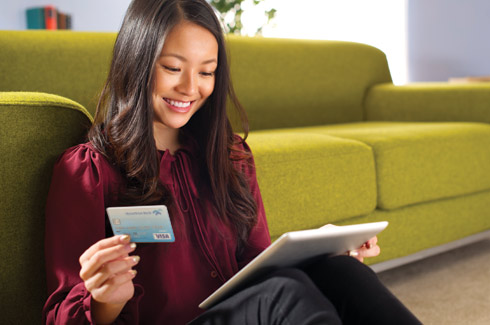 Woman using a tablet and hometrust debit card