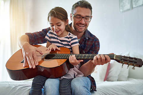Father teaching daughter how to play guitar