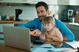 Father and young daughter paying bills