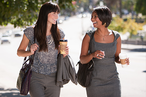 Two professional women walking down the street