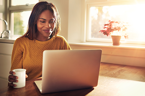 Smiling woman using laptop by windows