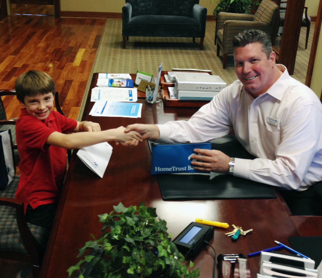7 year old customer shakes hands with banker