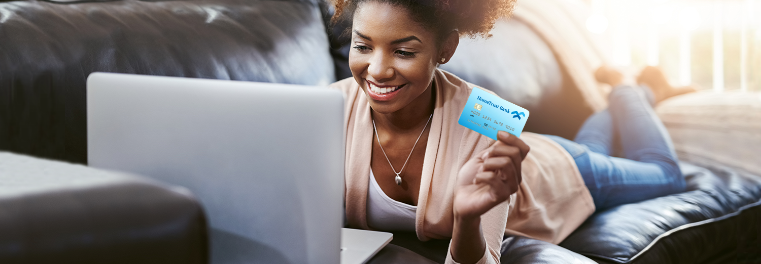 Smiling woman using HomeTrust debit card with a laptop