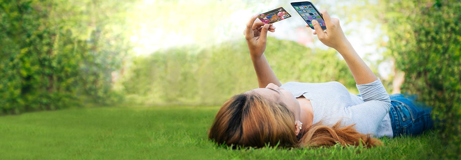 Woman in grass using phone and HomeTrust debit card
