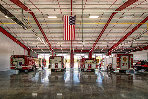 Fire trucks parked inside a fire station.