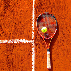 Tennis racket on a clay court