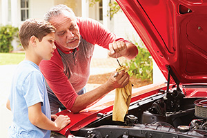 Grandfather and grandson working on a car